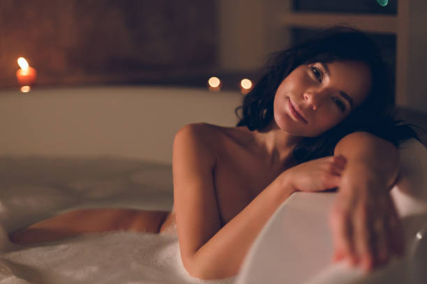Sensual young woman relaxing taking a bath in luxury hotel room stock photo