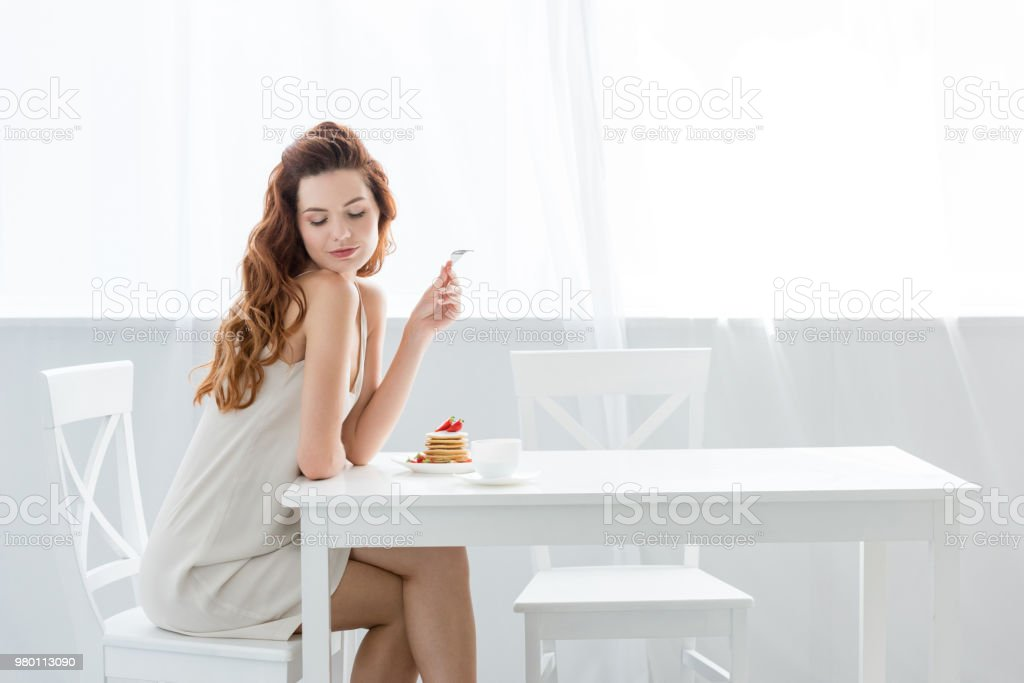 sensual young woman sitting at table with strawberry pancakes at home stock photo