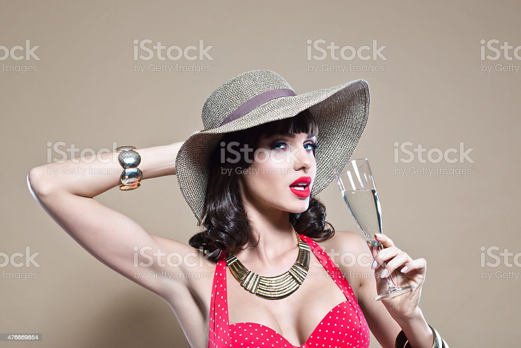 Sensual young woman wearing sun hat holding a champagne glass stock photo