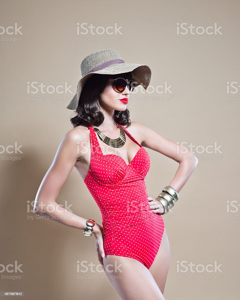 Sensual young woman wearing swimwear, sunhat and sunglasses stock photo