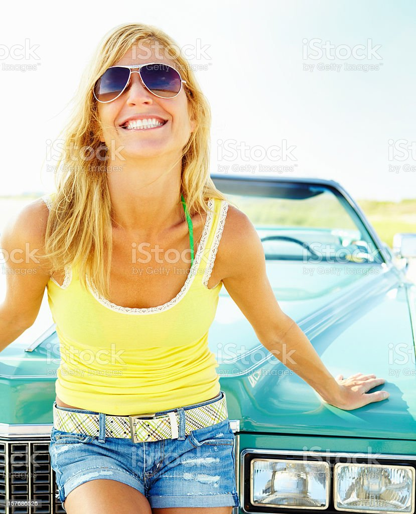 Sensuous young woman posing against convertible car royalty-free stock photo