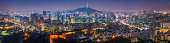 Panoramic view over the landmarks and lights of Seoul, Korea's crowded and colourful capital city, from the ancient fortress walls across the futuristic neon lights of downtown, past the iconic spire of Seoul Tower on Namsan mountain to the modern high rises of Gangnam and beyond.