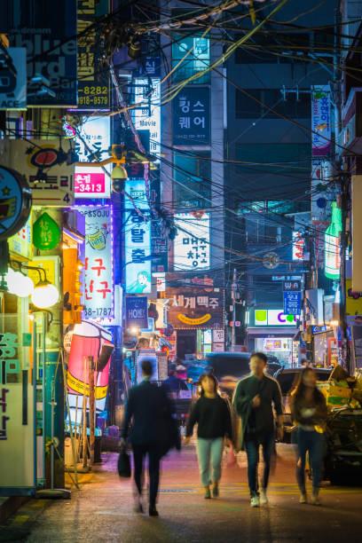 Seoul people on busy nightlife street Sinchon neon night Korea stock photo