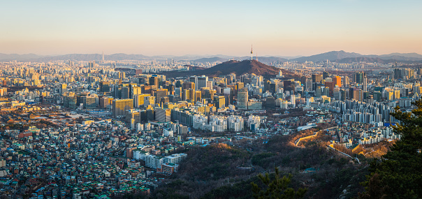 Aerial panorama over the crowded highrise cityscape of Seoul overlooked by the iconic spire of Namsan Tower in the heart of South Korea's vibrant capital city.
