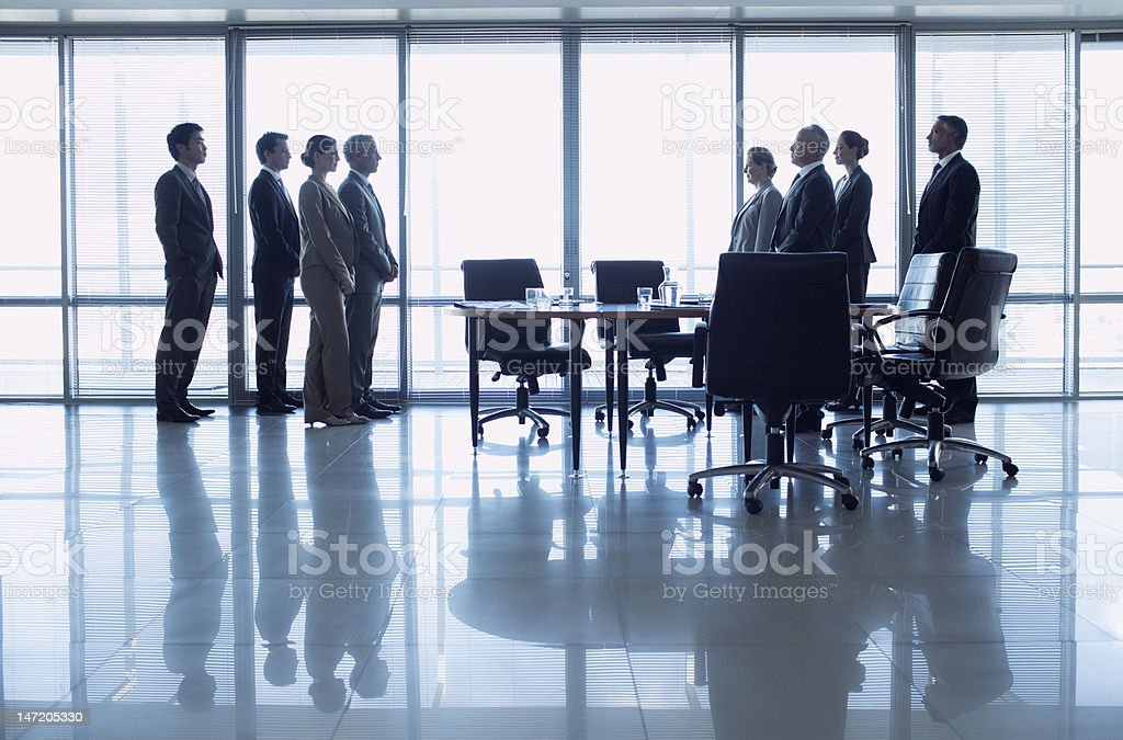 Separate groups of business people facing off in conference room stock photo