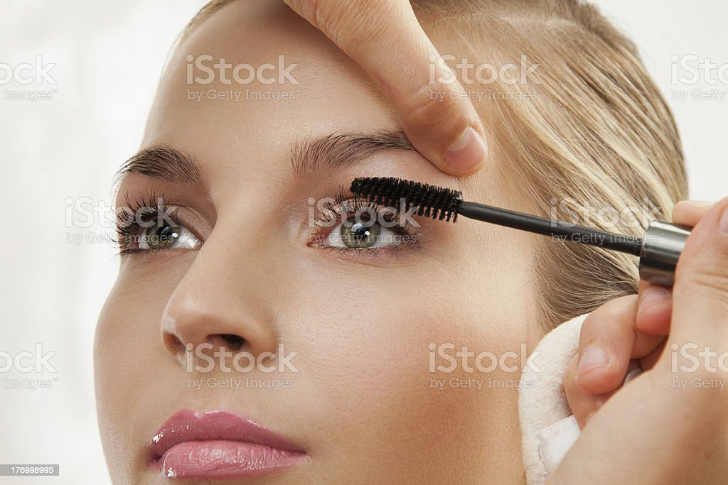 separating and curling lashes with mascara brush stock photo