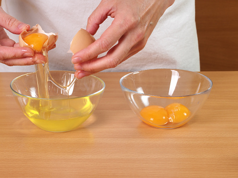 Separating egg yolk from white. Making Chocolate Layer Cake with Cream Cheese Filling and Chocolate Topping. Series.