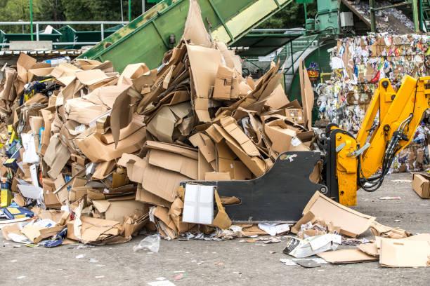 trennung von pappe im müll-recycling-center - papier recycling stock-fotos und bilder