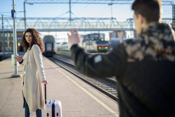 Separation of young couple woman leaving with suitcase at train station platform while boyfriend waving Separation of young couple woman leaving with suitcase at train station platform while boyfriend waving horizontal shot long distance relationship stock pictures, royalty-free photos & images