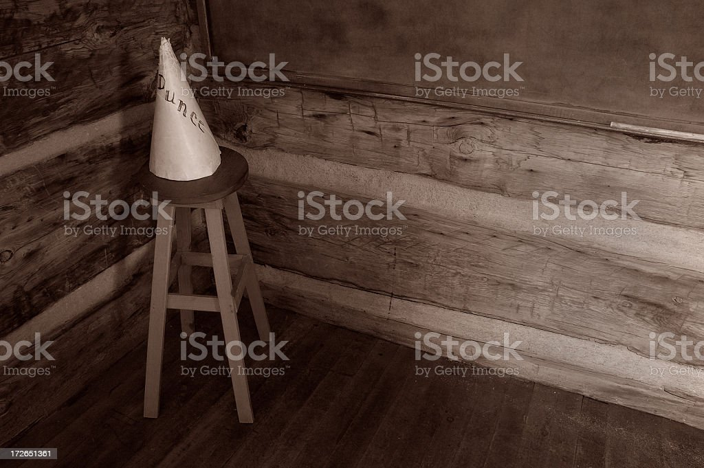 A sepia photo of a wooden room with a dunce cap on a stool stock photo
