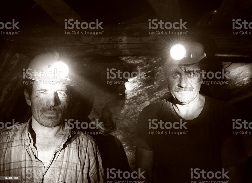 Sepia photograph of two miners posing inside a mine shaft stock photo