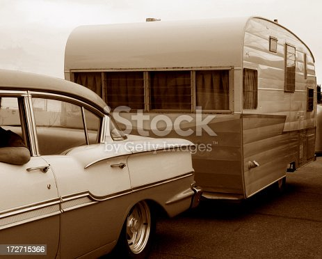 vintage automobile towing vintage travel trailer, in sepia