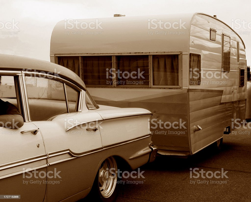 Sepia picture of an antique car pulling a trailer stock photo