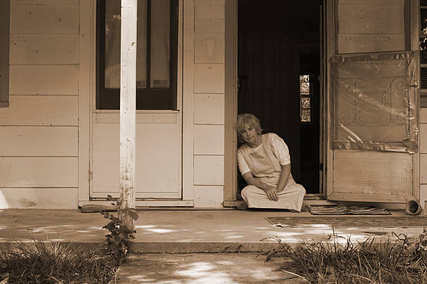 Sepia picture of elderly woman sitting at the doorstep stock photo