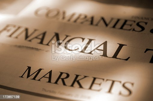 A sepia toned, close up image of a loosely stacked pile of sections of a generic financial broadsheet newspaper showing the sections headed 'Companies', 'Financial', and 'Markets'. Shot with shallow depth of field with focus on the centre right of the image.