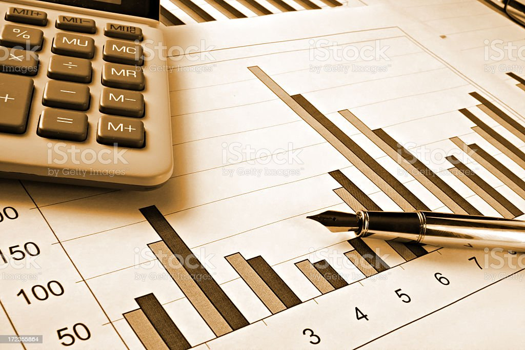 Sepia toned image of a graph, calculator and fountain pen royalty-free stock photo