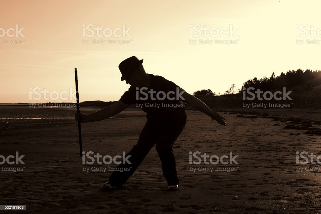 sepia toned image of man dancing on beach stock photo