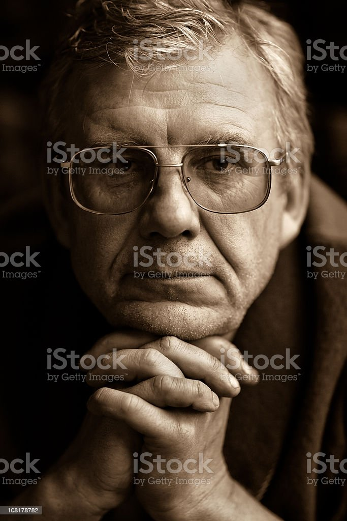 Sepia Toned Image of Older Man Leaning on Folded Hands royalty-free stock photo