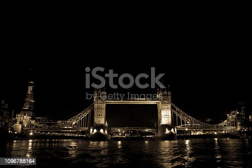 Night view of the famous Tower Bridge in London, as seen from a boat approaching the bridge.