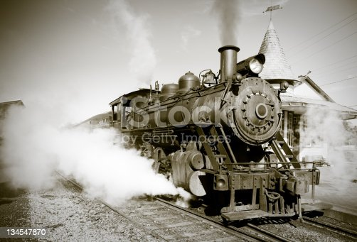 A sepia toned vintage steam locomotive begins it's journey from the station