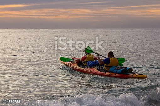 19 sept 2019 The Peninsula of the Crimea, Russia: athletes kayakers man and woman go on a kayak trip on the Bay of Black sea to meet the beautiful sunset. Amazing views. Perfect activity for holidays. Ukraine.