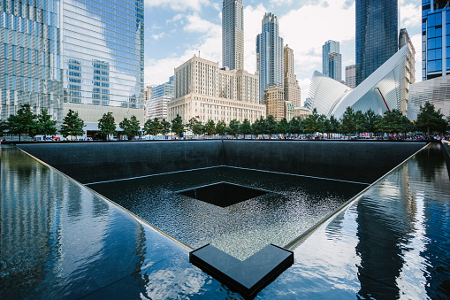 New York, USA - September 7, 2016:  South pool memorial commemorating the victims of the 11 september terror attack in 2001. New York architecture in the background.