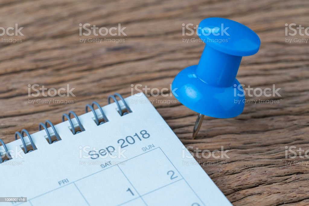 September 2018 appointment, deadline, holiday or date planning concept, big blue pushpin or thumbtack pin on wooden table next to Sep white clean calendar stock photo