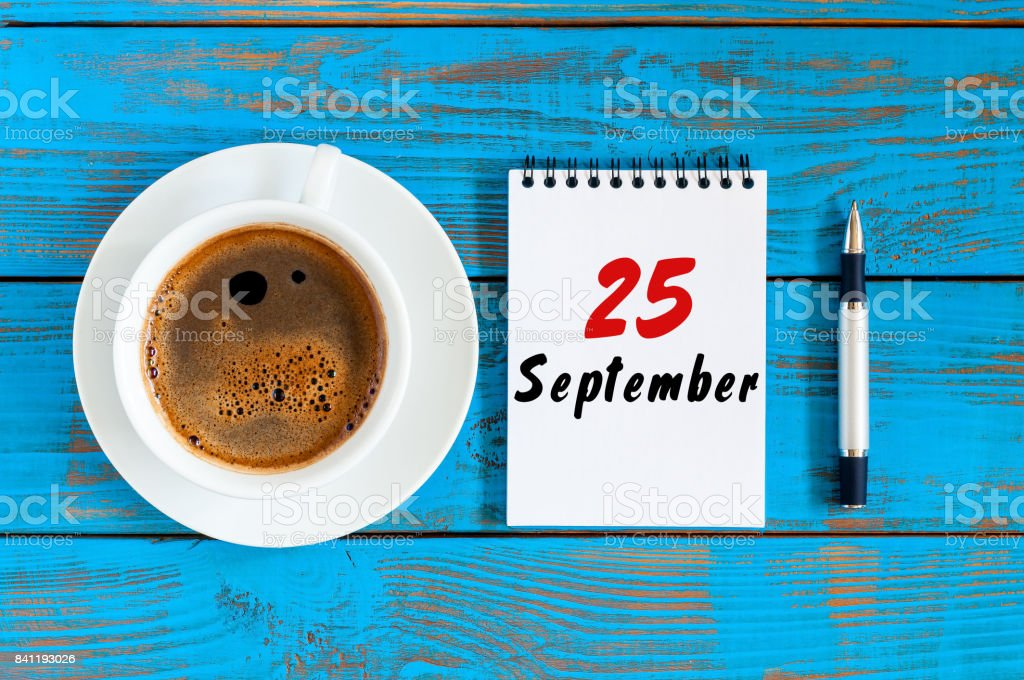 September 25th. Day 25 of month, loose-leaf calendar and cappuccino cup at Administrator workplace background. Autumn time. Empty space for text stock photo