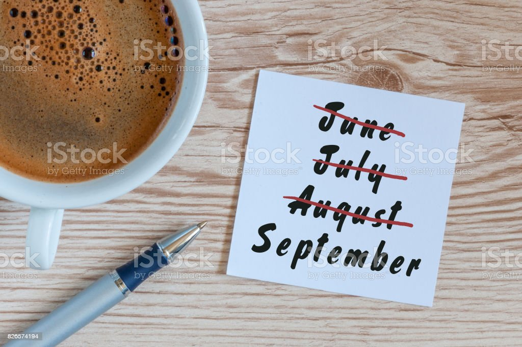 September beginning and summer end concept written at notepad with morning cup of coffee. Striked June, July, August September beginning and summer end concept written at notepad with morning cup of coffee. Striked June, July, August. Abstract Stock Photo