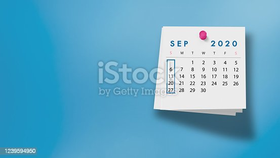 2020 September calendar on a white note paper pinned on wall against blue background. High resolution and copy space for all your crop needs.
