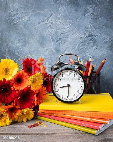 istock 1 September concept postcard, teachers' day, back to school or college, supplies, alarm clock, a bunch of gerbera 950456226