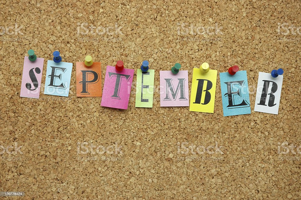 September spelled out in post its tacked to a cork board stock photo