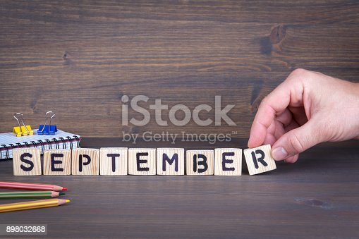 istock september. Wooden letters on the office desk, informative and communication background 898032668