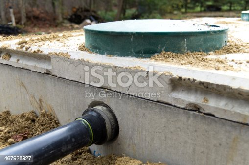 View of sewage drainage pipe from house entering a cement septic tank.