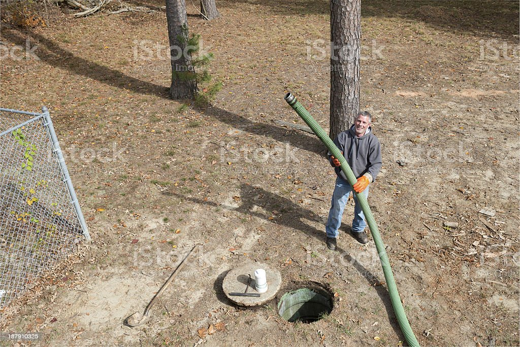 Septic Tank Worker Holds Sewage Hose royalty-free stock photo