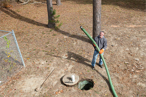 Septic Tank Worker Holds Sewage Hose stock photo