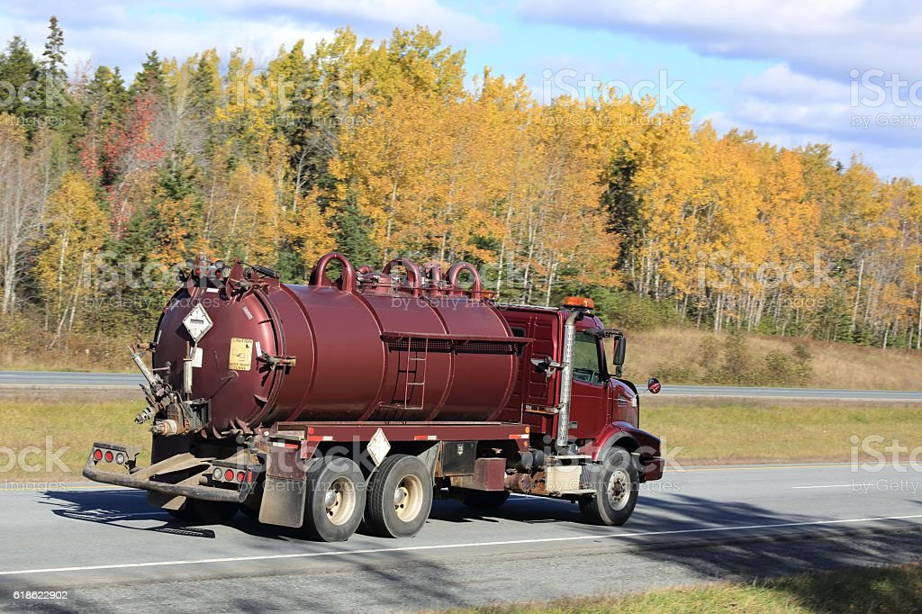 Septic truck being driven,  trees in background stock photo