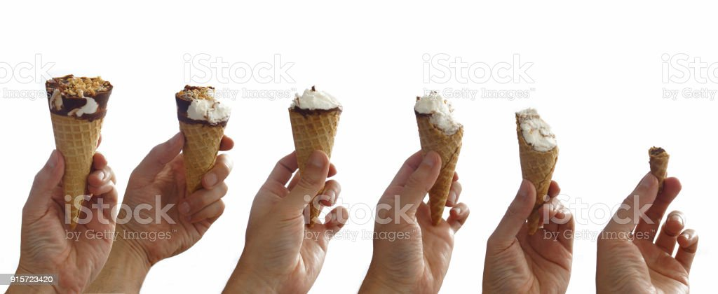 Sequence of an ice cream being eaten step by step. Man's hand holding a chocolate covered vanilla ice cream cone with peanut stock photo