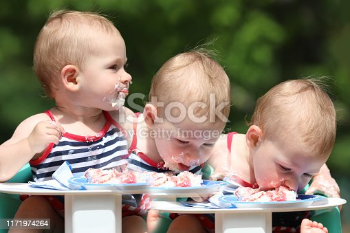 Sequential series of Baby eating birthday cake at picnic