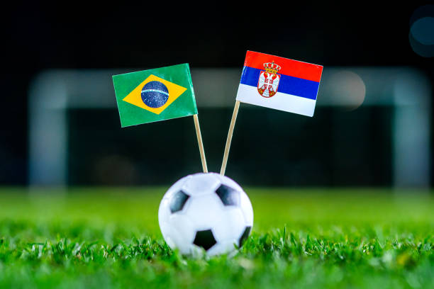 serbia - brazil, group e, wednesday, 27. june, football, world cup, russia 2018, national flags on green grass, white football ball on ground. - serbia stock photos and pictures