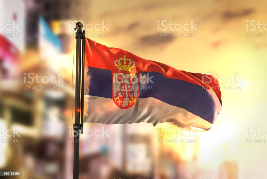 Serbia Flag Against City Blurred Background At Sunrise Backlight - fotografia de stock