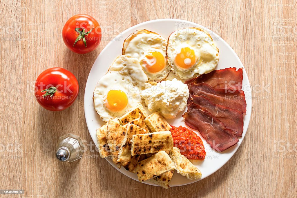 Serbian breakfast with eggs, ham, cheese, ajvar and homemade bread stock photo