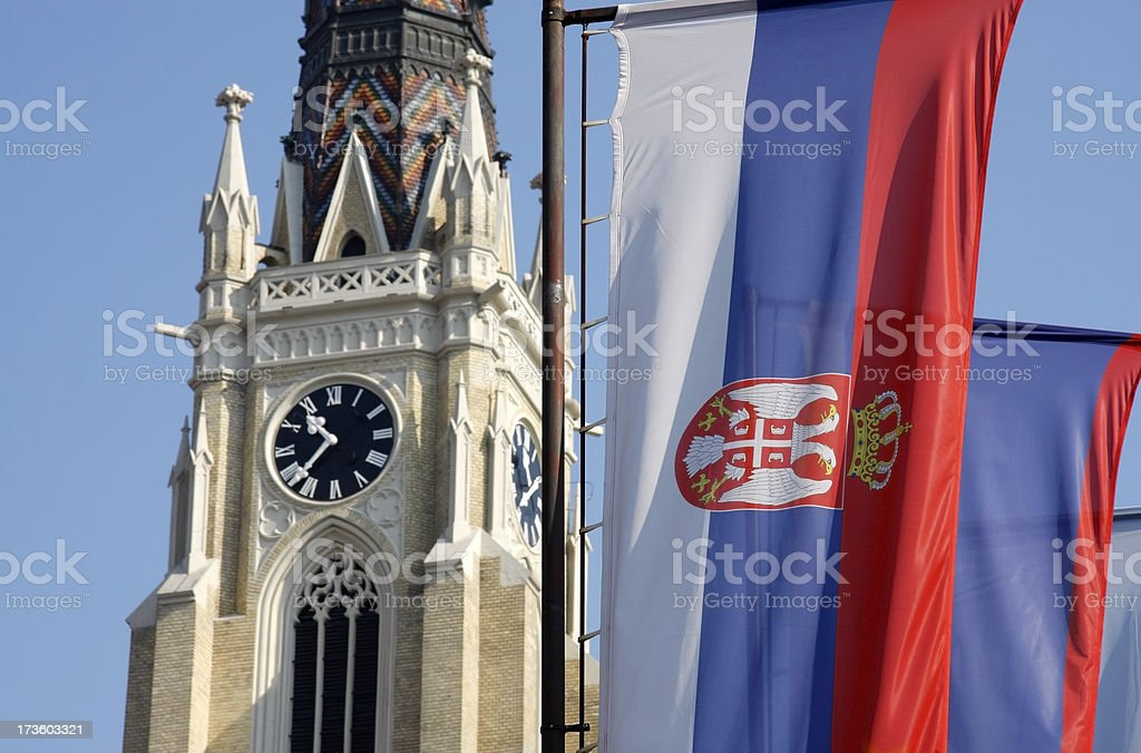 Serbian flag flying in front of a clock tower stock photo