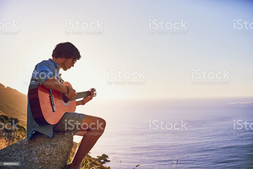 Serenading the sea Shot of a young man playing the guitar while sitting at a viewpoint outside 20-29 Years Stock Photo