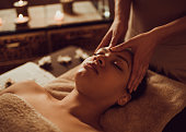 Serene African American woman receiving head massage at beauty spa.