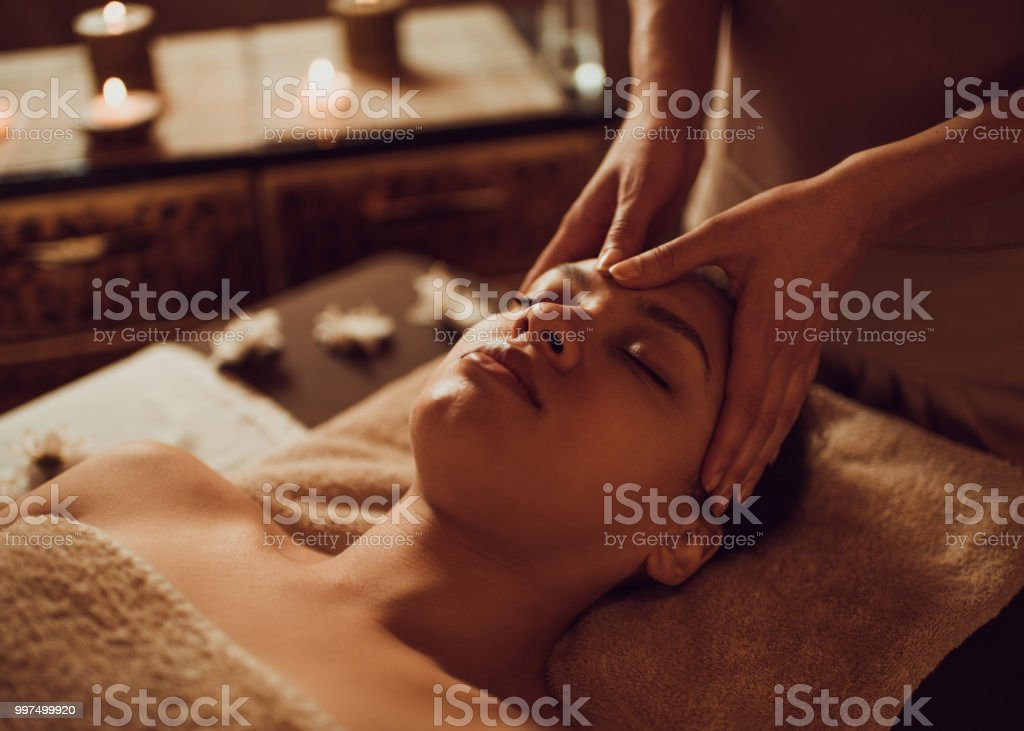 Serene African American woman receiving head massage at beauty spa. stock photo