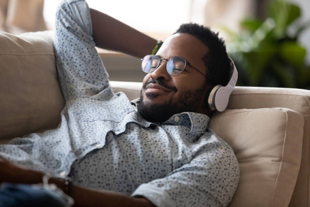 Serene african man lying on sofa wear headphones listen music Serene satisfied young adult african american man lying on comfortable sofa wear wireless headphones enjoy listen modern music audio book with eyes closed meditate relax feel no stress chill at home wireless headphones stock pictures, royalty-free photos & images