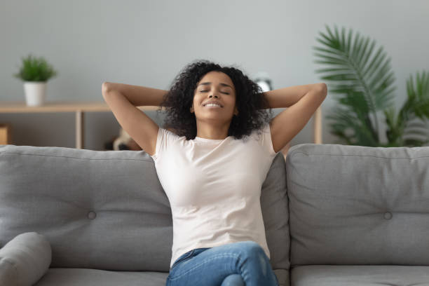 Serene african woman leaned on couch resting at home Tranquil attractive mixed-race 30s woman closed eyes fall asleep or do meditation exercise feel placidity and inner balance harmony, spend free time at home enjoy rest peace of mind and body concept relief emotion stock pictures, royalty-free photos & images