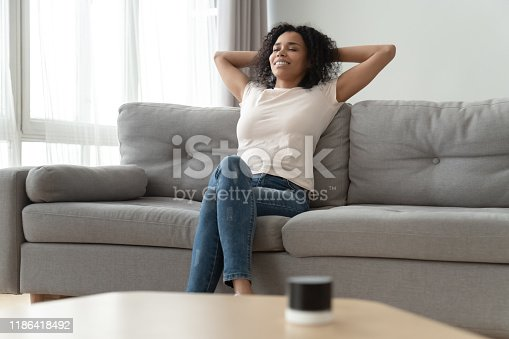 1143763067istockphoto Serene african woman leaned on couch resting in living room 1186418492