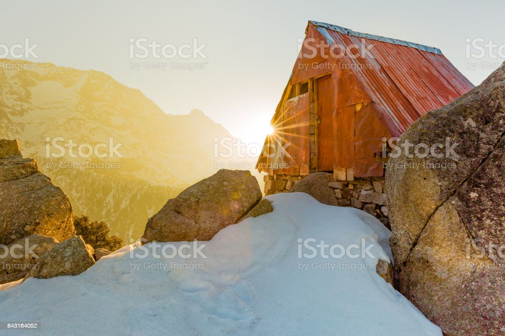 Serene and beautiful Cabin in the snow mountains at Triund hill top, Mcleod ganj, Dharamsala, India during amazing sunrise from behind the snow mountains in winter. Sun burst, dawn break, golden hour stock photo